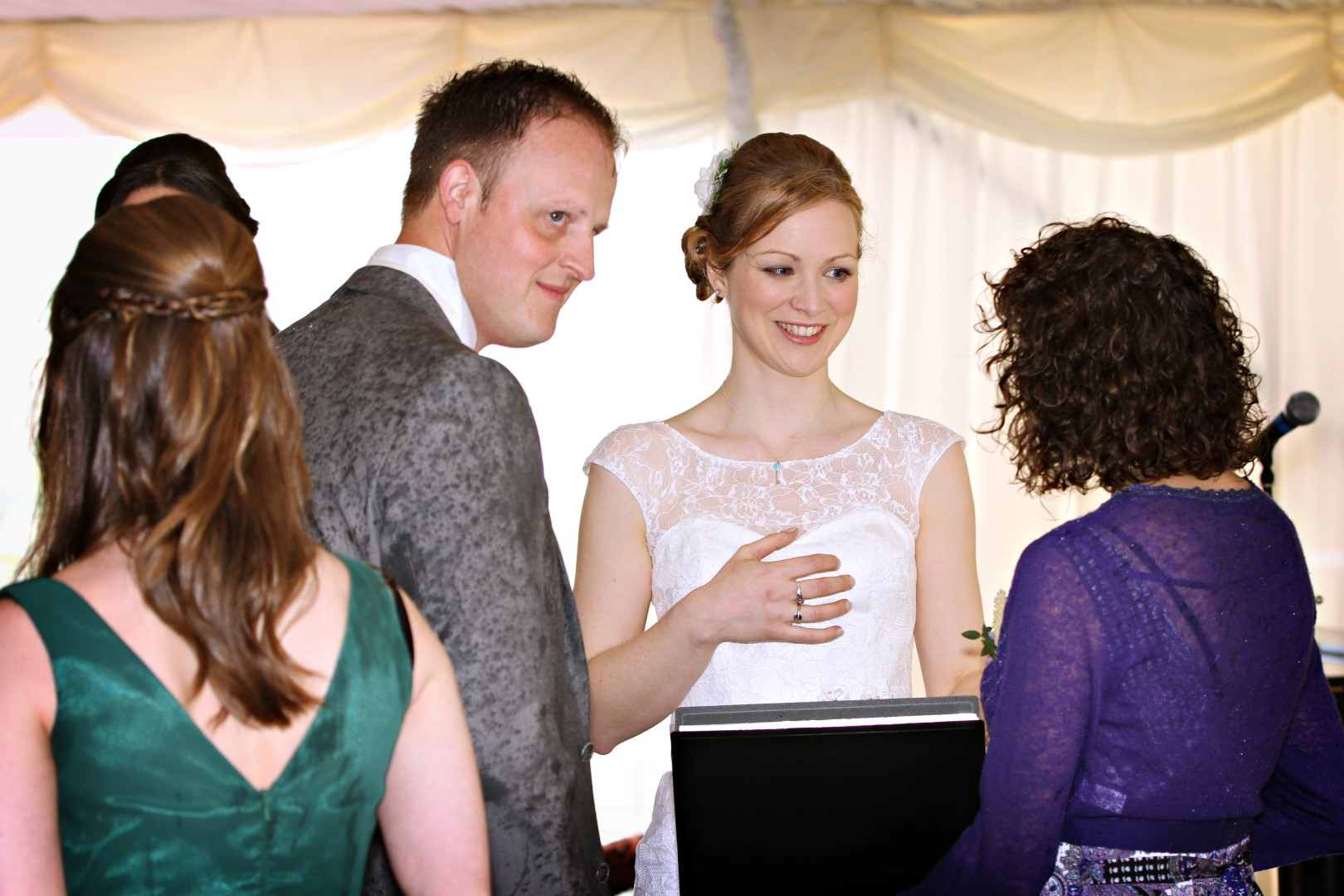 A bride and groom stand with their Celebrant Keli Tomlin. The Bride is smiling at Keli as she speaks. The groom is looking away into the distance, watching something unseen.