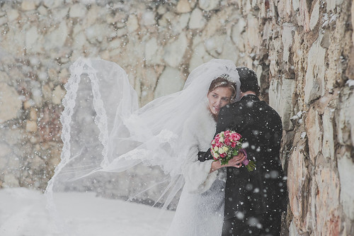 A Bride and Groom stand outside next to a tall stone wall. The groom's back is to the camera, the bride is embracing him and peering over his shoulder to the distance. Her veil is being blown out beside her by the wind. There is snow falling.