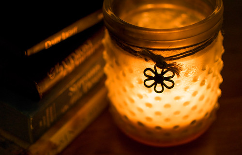 A teaclight candle lights up a glass holder which had dots on the frosted glass and a small daisy charm attached to sting around the jar rim. Beside the jar is a pile of books.