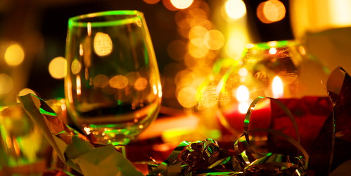 Close up of an empty wine glass with torn wrapping paper in the foreground. Behind is candle light and darkness.
