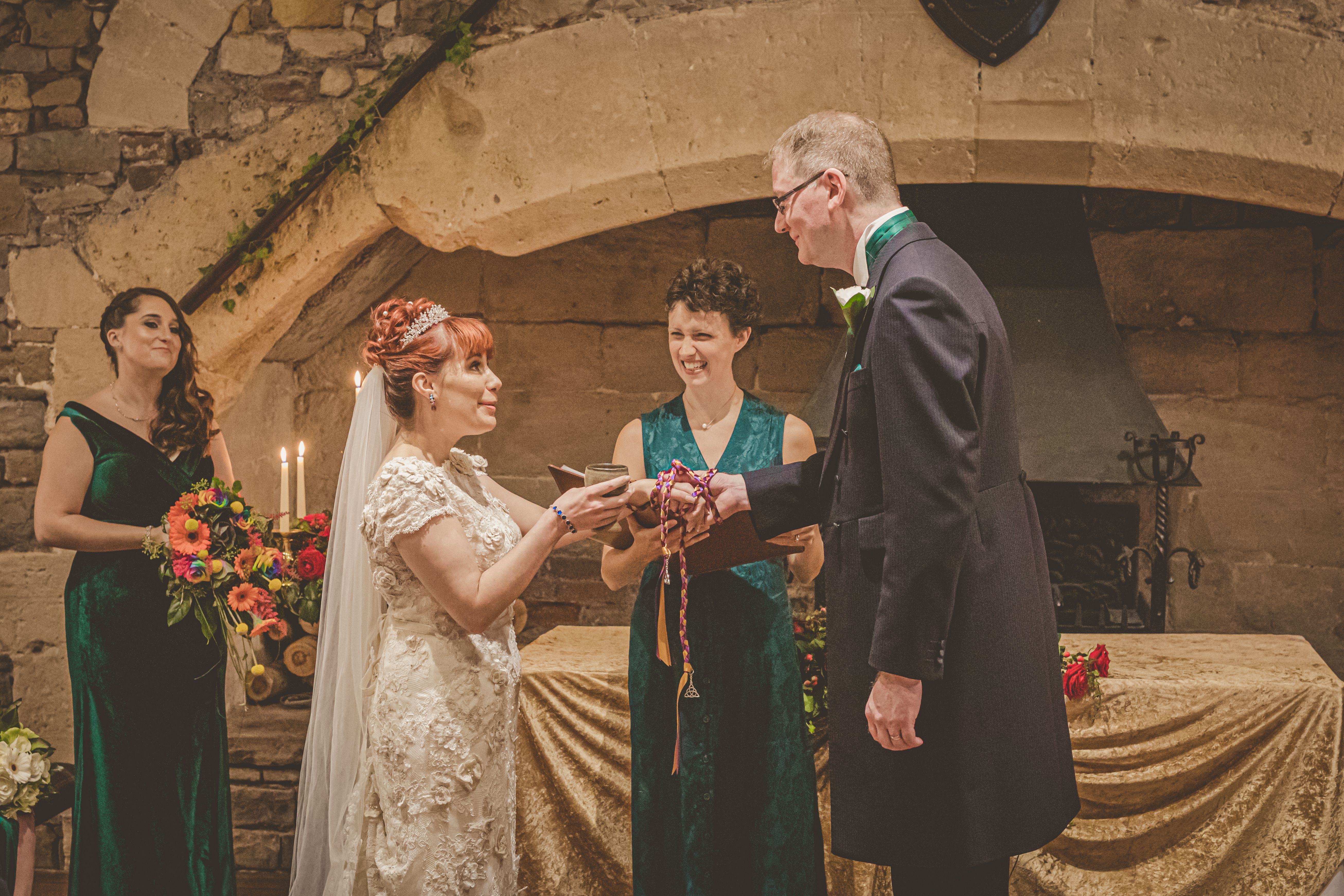A Bride and Groom stand before a large stone fireplace. The Celebrant Keli Tomlin is standing behind them, laughing at something the bride has said. The couple's hands are tied with a purple and gold handfasting cord.
