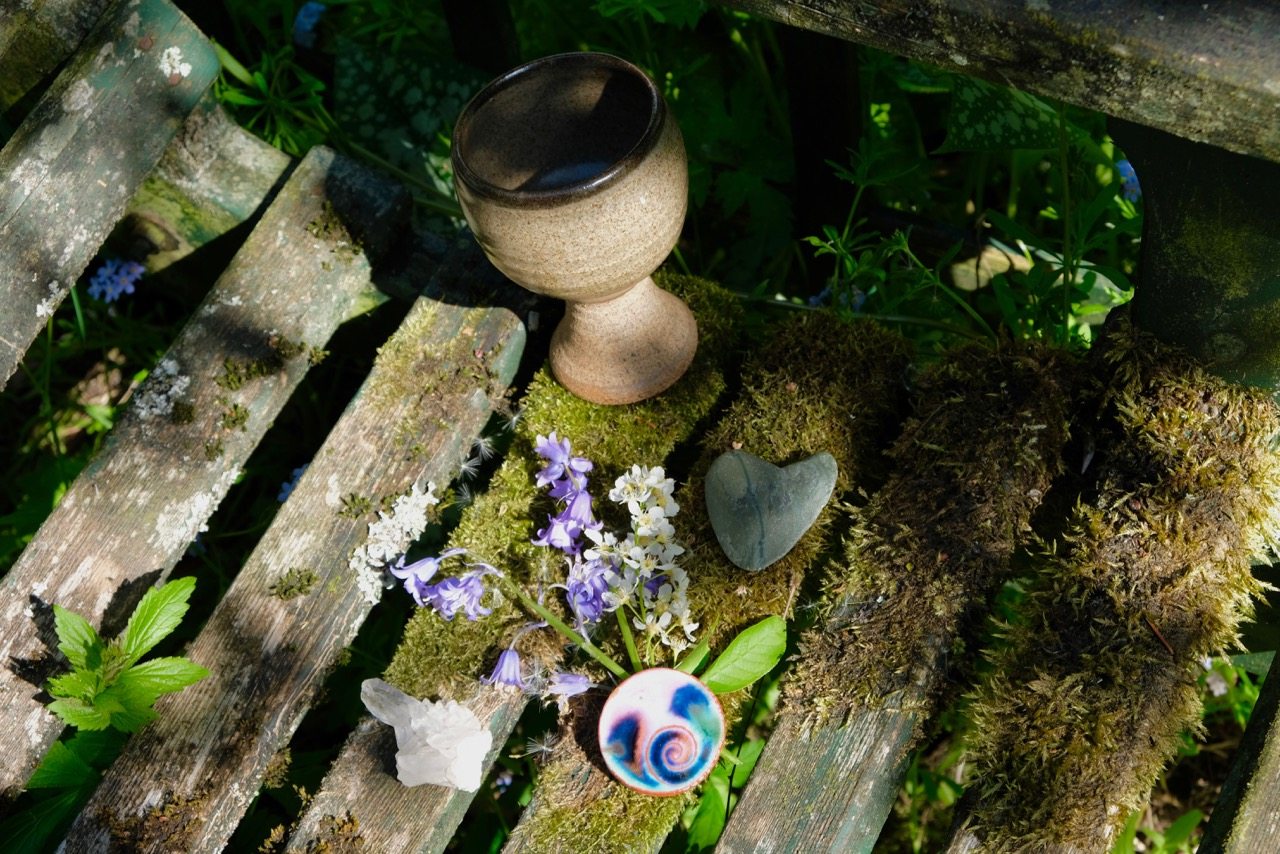 A stone chalice filled with water stands on a mossy old bench, beside it is a heart shaped stone, a ceramic pendant with a swirl motif, a piece of quartz crystal and a small bunch of flowers. A small altar by Keli Tomlin