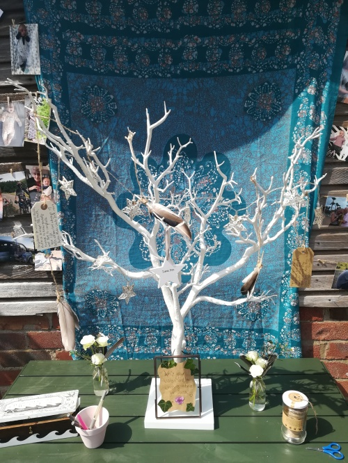 A small white fake tree with bare branches, hung with feathers, charms and luggage tags stands on a green table in front of a wooden wall decorated with a blue cloth. A wishing tree for a Naming Ceremony by Keli Tomlin