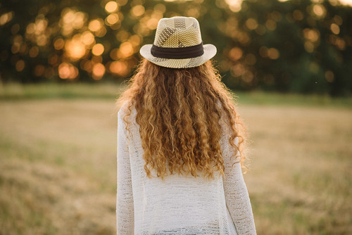 a woman wearing a long white cardigan stands beside a mown field, looking towards a sun setting through trees. her long blonde hair falls down her back. she is wearing a white trilby hat with a black band