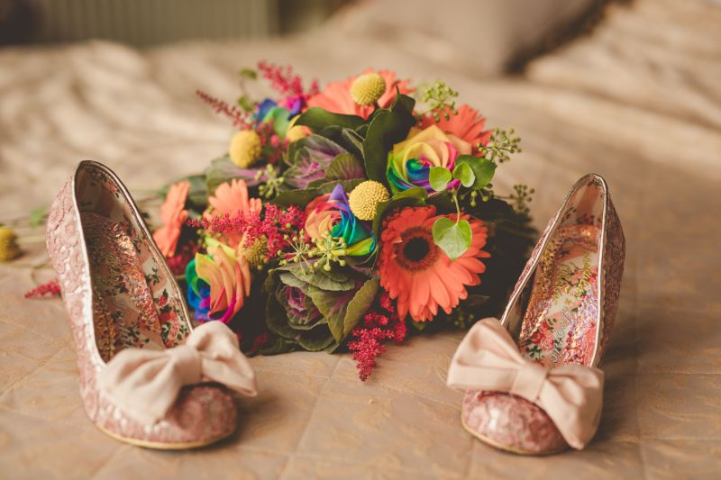 A pair of buff wedding shoes with large bows and floral insides sit on a white bedspread, between them is a vibrant, rainbow coloured bouquet with orange gerberas and rainbow coloured roses. From a wedding by Keli Tomlin Ceremonies