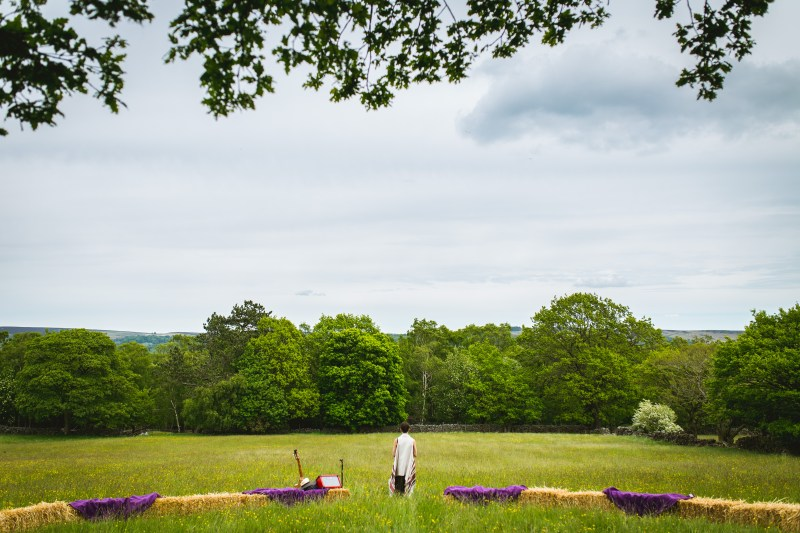 a grassy meadow with trees at the bottom and a lot of blue sky. in the foregrounds a line of haybales cut across, ready to be sat upon by wedding guests. standing at the centre of this line, looking away with back to camera is pagan celebrant Keli Tomlin