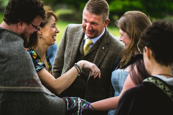 A man and woman laugh with the bride and groom who are in the process of being handfasted; their hands are tied together with many colourful ribbons. Part of a Handfasting by Keli Tomlin Ceremonies