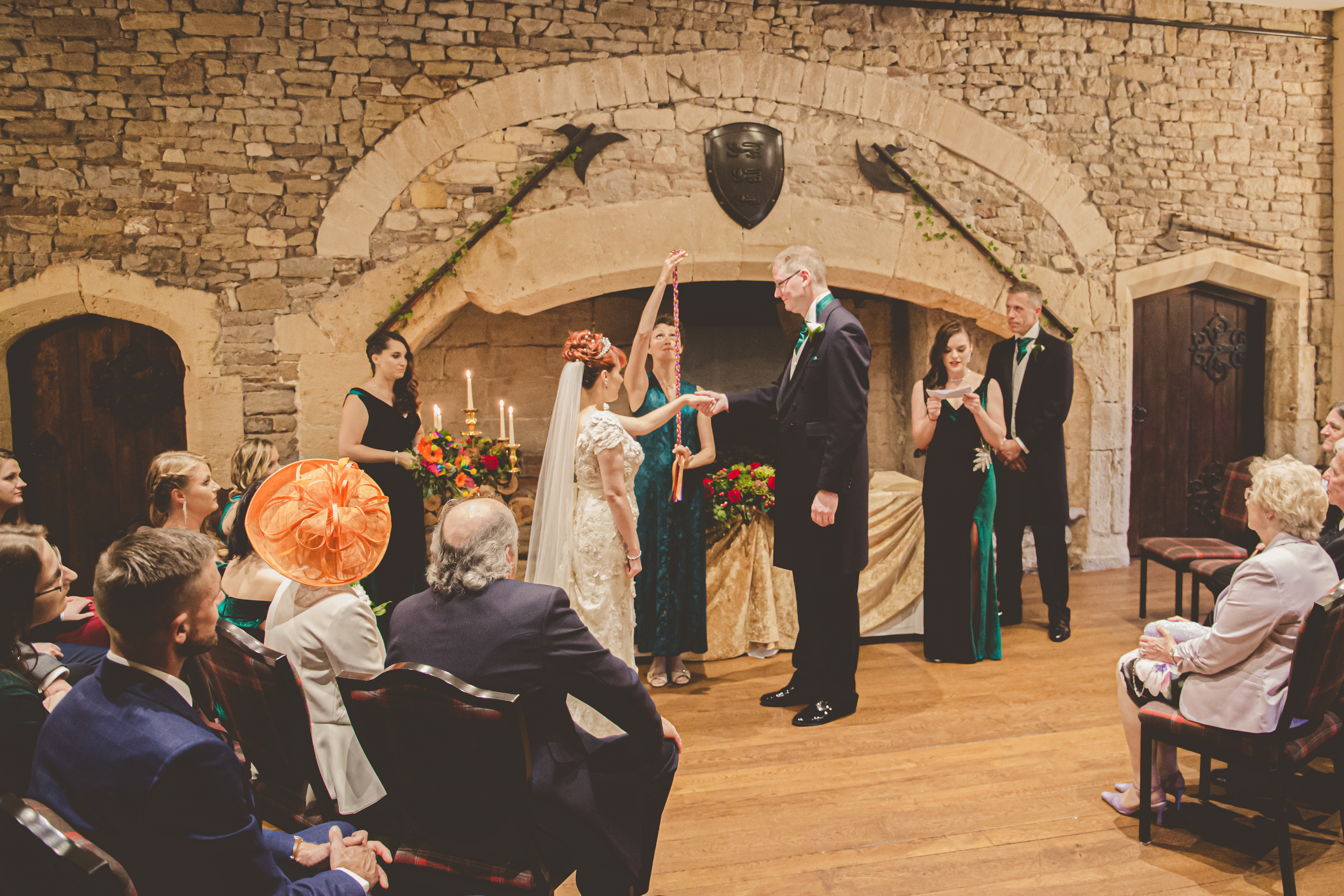 A bride and groom stand with their hands joined while Celebrant Keli Tomlin Holds up the handfasting cord ready to bind their hands. The guests look on. They are standing before a large stone fireplace in Thornbury Castle with shields hanging on the wall.