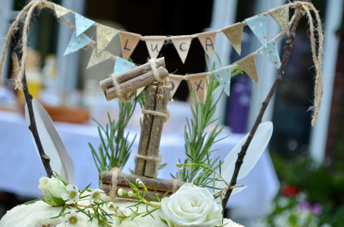 A Number 1 cake topper made from sticks, sits beneath a small bunting cake topper in blue and hessian brown. The very top of the cake is white and also visible. There are two real feathers and some rosemary sprigs sticking up from the cake also.