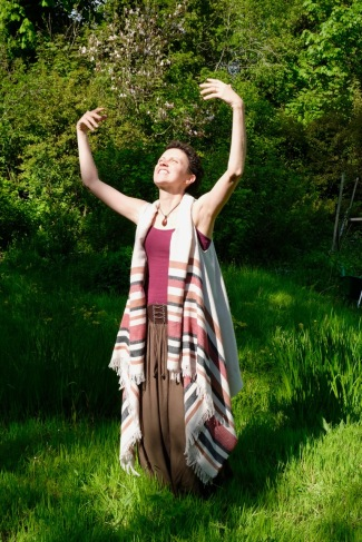a woman, keli tomlin, stands amongst trees and grass, wearing a long green skirt, purple vest and long white jacket. her arms are raised to the sky and her face turned upward. she is smiling at the sun.