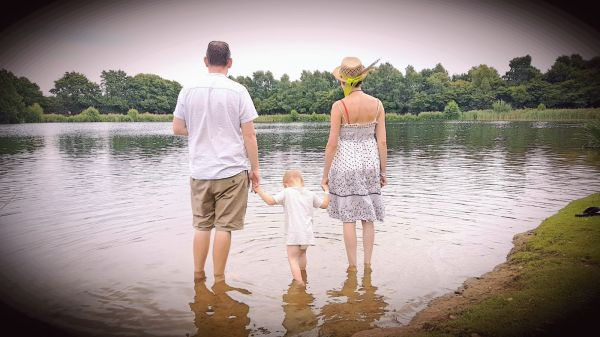 a man, woman and small child stand barefoot in the water of a lake with their backs to the camera. the child is in the middle holding the adults' hands.