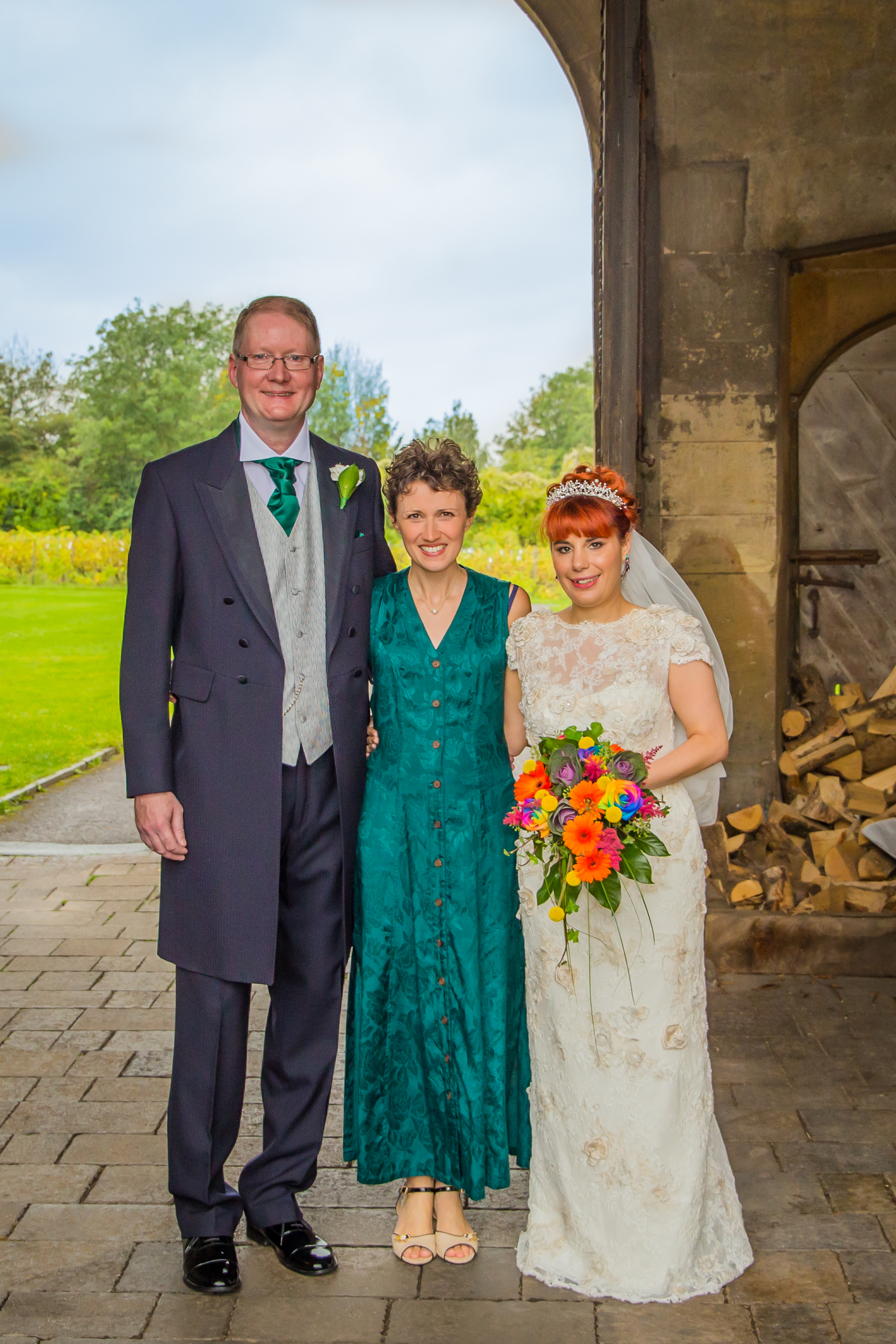 Wedding Celebrant Keli Tomlin stands with a bride and groom in the entrance to Thornbury Castle. The sky showing behind them is cloudy, the bride is carrying a brightly coloured bouquet.